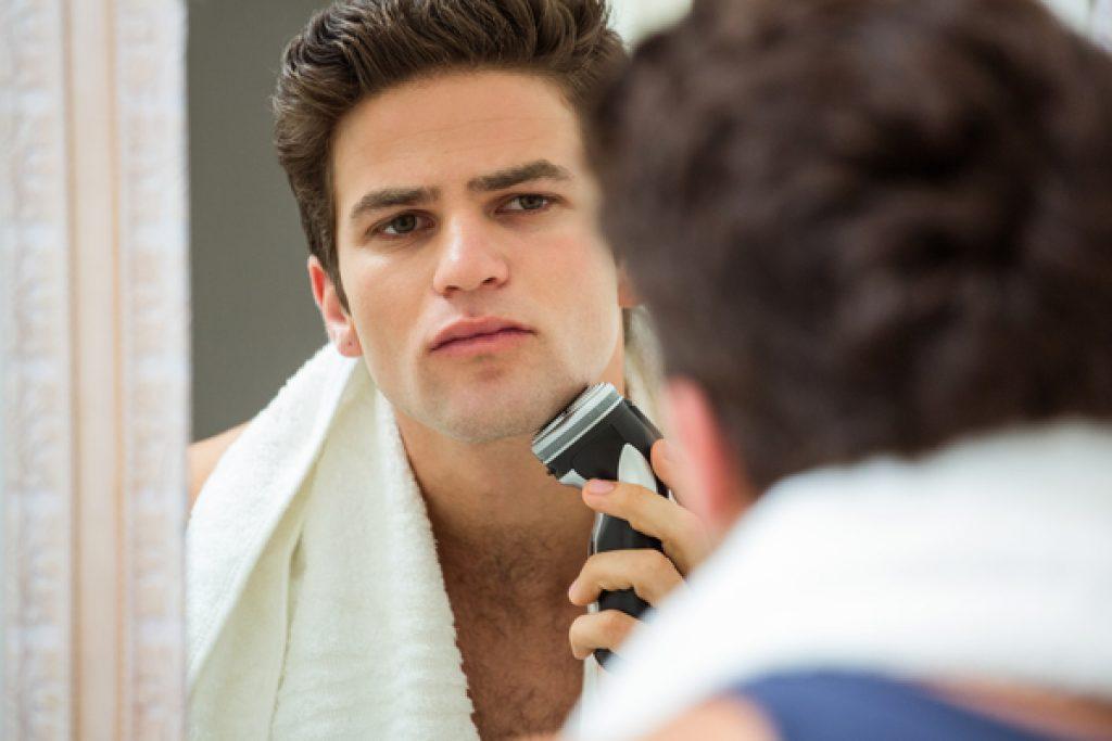 Mann rasiert sich die Barthaare mit einem Trimmer