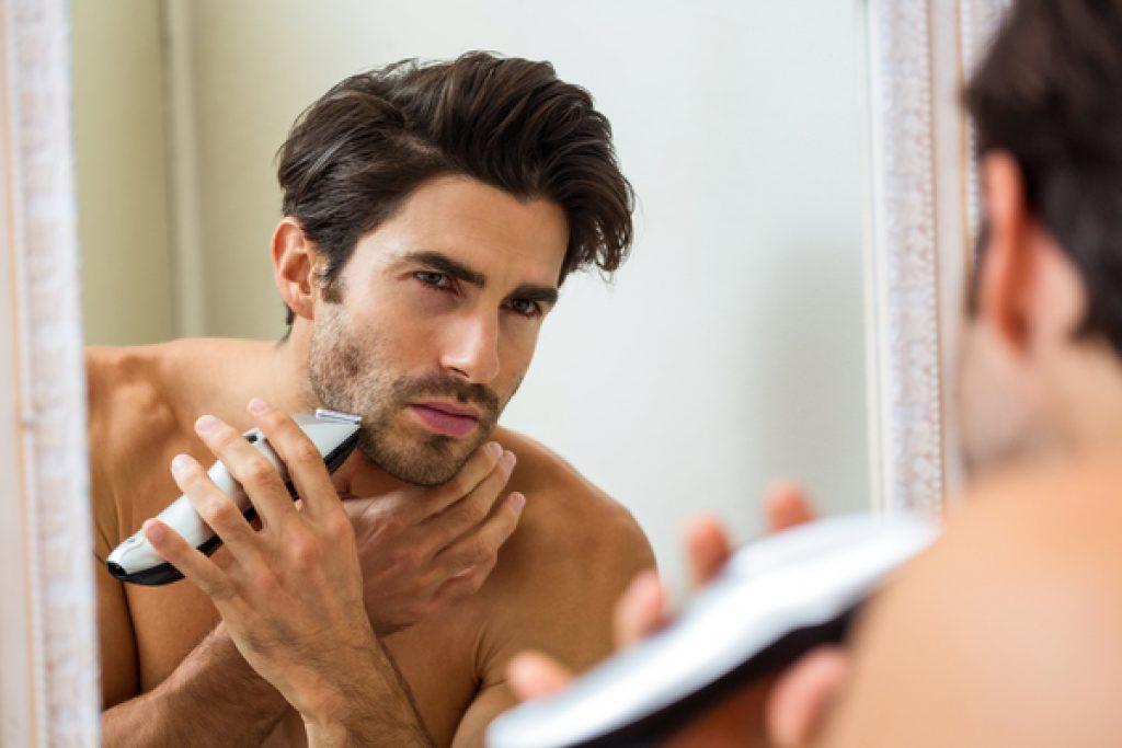 Mann trimmt sich mit einem Barttrimmer das Gesicht